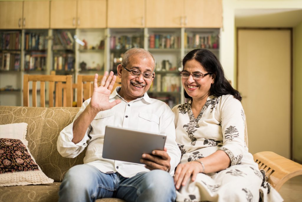 An older couple using a tablet to video chat.