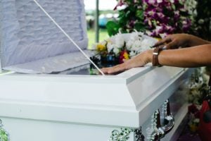 Hands on a casket covered in flowers