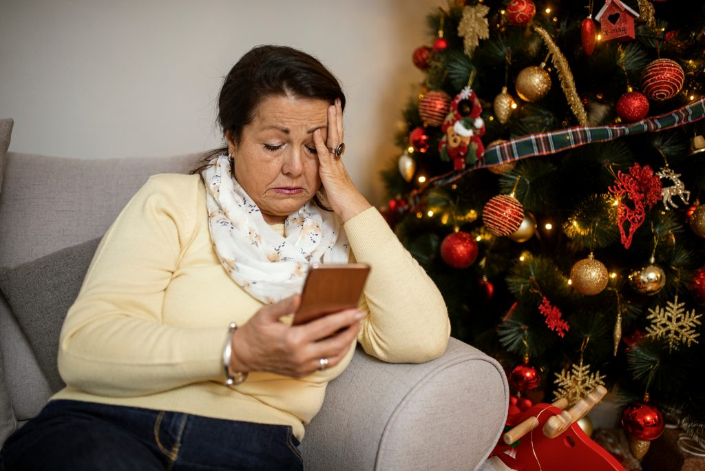 Woman looking sad in front of Christmas tree.