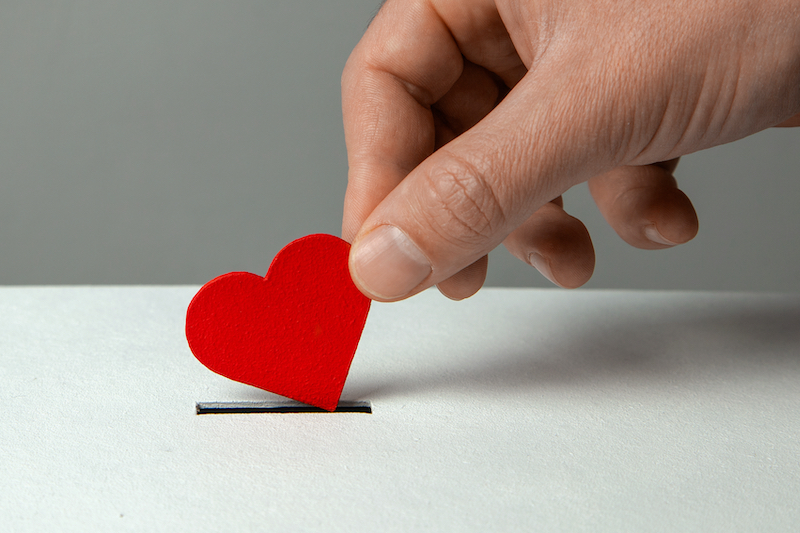 Hand placing a heart in a box